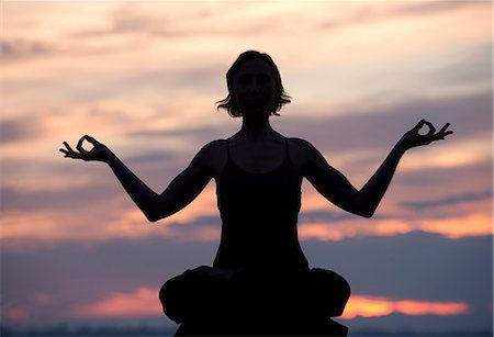 Silhouette of woman in lotus position at sunset Stock Photo - Premium Royalty-Free, Code: 614-06116384
