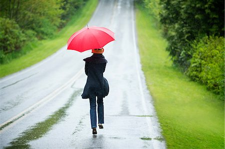 people with umbrellas in the rain - Woman on empty road with red umbrella Stock Photo - Premium Royalty-Free, Code: 614-06116456