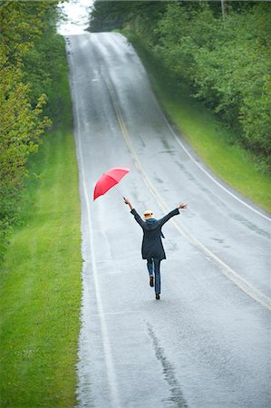 people with umbrellas in the rain - Woman on empty road with red umbrella Stock Photo - Premium Royalty-Free, Code: 614-06116457
