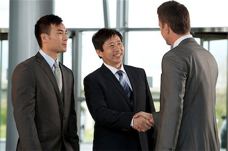 Multiracial businessmen shaking hands Stock Photo - Premium Royalty-Free, Code: 614-06116471