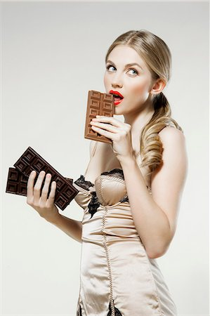Young woman biting chocolate Stock Photo - Premium Royalty-Free, Code: 614-06168625