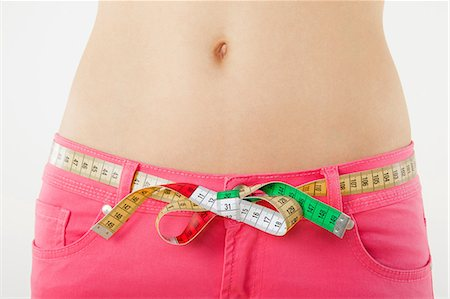slim - Young woman measuring waist with tape measure Stock Photo - Premium Royalty-Free, Code: 614-06168631