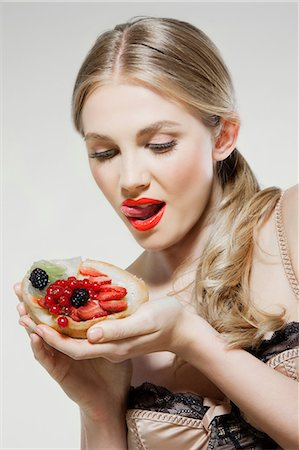 Young woman eating fresh fruit tart Stock Photo - Premium Royalty-Free, Code: 614-06168646