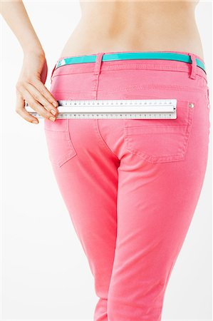 Young woman measuring buttocks Stock Photo - Premium Royalty-Free, Code: 614-06168647