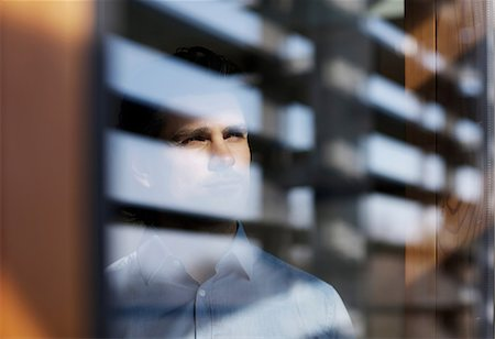 Businessman looking through window Stock Photo - Premium Royalty-Free, Code: 614-06168716