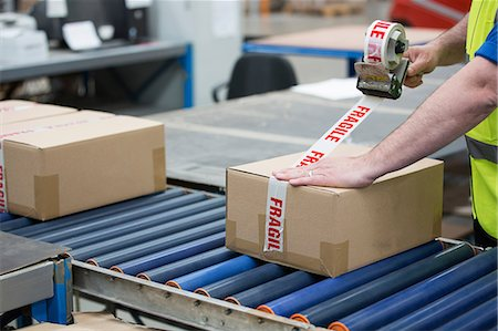 fragile - Man packing cardboard box in warehouse Stock Photo - Premium Royalty-Free, Code: 614-06168797