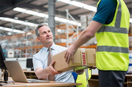fragile - Man delivering cardboard box to another man Stock Photo - Premium Royalty-Free, Code: 614-06168808