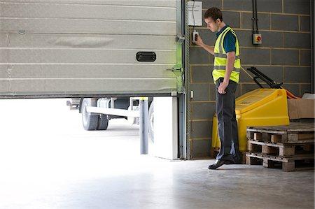 Man opening warehouse doors Stock Photo - Premium Royalty-Free, Code: 614-06168825