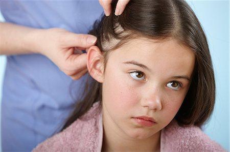 sad girls - Parent checking daughter's hair for headlice Stock Photo - Premium Royalty-Free, Code: 614-06168879