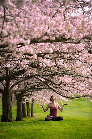 Woman in lotus position under cherry tree Stock Photo - Premium Royalty-Free, Code: 614-06168935