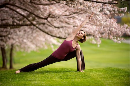 Woman in side angle yoga position under cherry tree Stock Photo - Premium Royalty-Free, Code: 614-06168936
