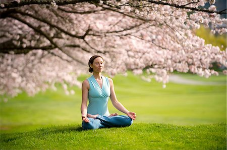Woman in lotus position under cherry tree Stock Photo - Premium Royalty-Free, Code: 614-06168930