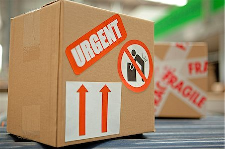 Cardboard box with warning stickers on conveyor belt Stock Photo - Premium Royalty-Free, Code: 614-06169128