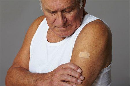 Senior man with plaster on arm Stock Photo - Premium Royalty-Free, Code: 614-06169263