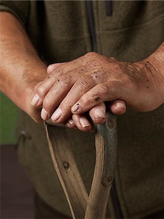 dirty - Man leaning with hands on wooden handle Stock Photo - Premium Royalty-Free, Code: 614-06169326