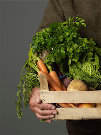 Man holding wooden crate of vegetables Stock Photo - Premium Royalty-Free, Code: 614-06169327