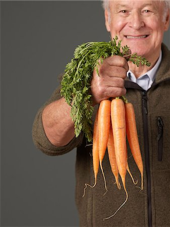 Man holding bunch of carrots Stock Photo - Premium Royalty-Free, Code: 614-06169321