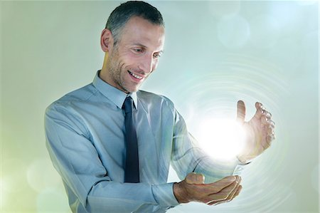 Businessman holding ball of light Stock Photo - Premium Royalty-Free, Code: 614-06169334