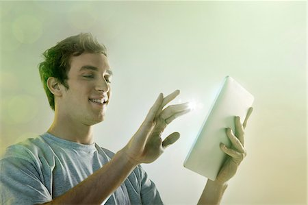 fingers holding - Young man using digital tablet with lights Stock Photo - Premium Royalty-Free, Code: 614-06169336
