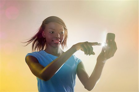 fingers holding - Teenage girl using illuminated cellphone Stock Photo - Premium Royalty-Free, Code: 614-06169331