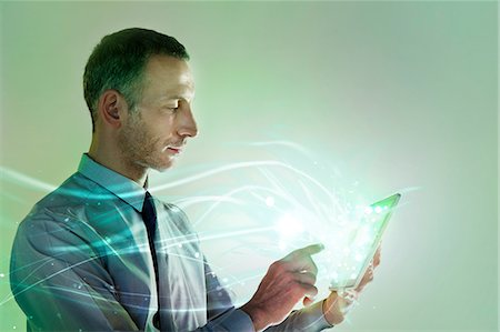 fibre optic - Businessman using digital tablet with lights Stock Photo - Premium Royalty-Free, Code: 614-06169333