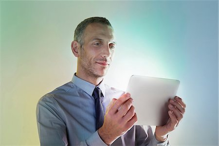 Businessman using digital tablet with lights Stock Photo - Premium Royalty-Free, Code: 614-06169342