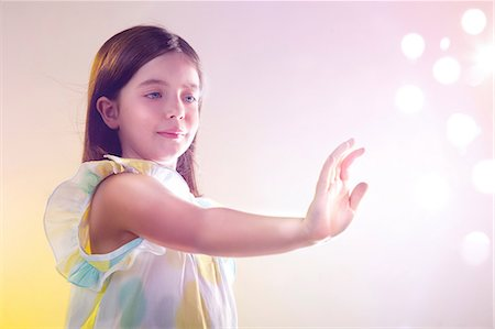 reaching - Girl reaching out to lights Stock Photo - Premium Royalty-Free, Code: 614-06169356