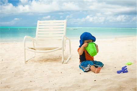 Little boy at the beach, looking into a bucket Stock Photo - Premium Royalty-Free, Code: 614-06169425