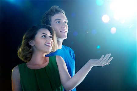 Young couple looking up at light Stock Photo - Premium Royalty-Free, Code: 614-06169439