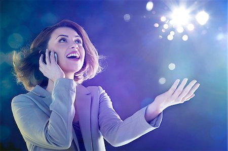 surprised - Young woman on cellphone, looking up at lights Stock Photo - Premium Royalty-Free, Code: 614-06169433