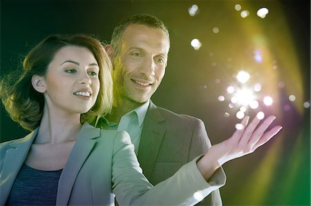 futuristic - Businesspeople reaching out to lights Stock Photo - Premium Royalty-Free, Code: 614-06169446