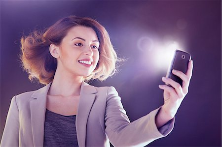 Young woman looking at cellphone with lights Stock Photo - Premium Royalty-Free, Code: 614-06169447
