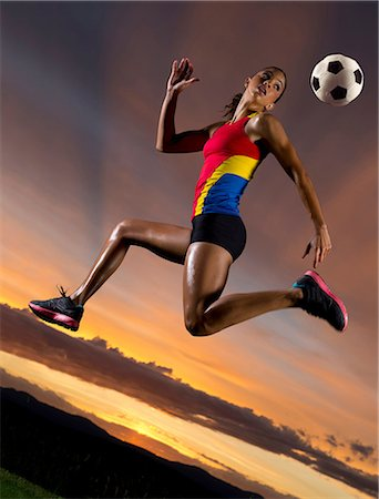 footballeur - Female footballer in mid air against sunset Stock Photo - Premium Royalty-Free, Code: 614-06169453