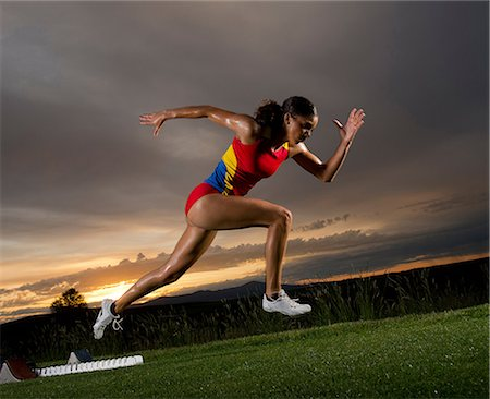 race track (people) - Female athlete leaving starting blocks Stock Photo - Premium Royalty-Free, Code: 614-06169464