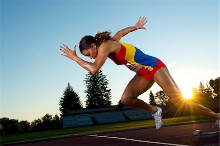 race track (people) - Female athlete leaving starting blocks Stock Photo - Premium Royalty-Free, Code: 614-06169462