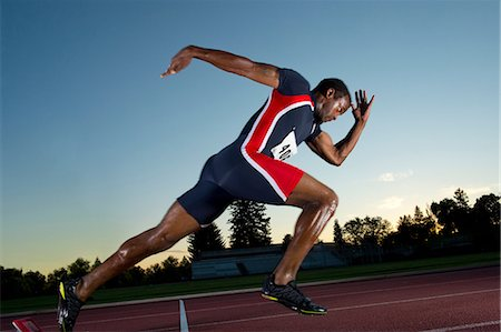 Male athlete leaving starting blocks Stock Photo - Premium Royalty-Free, Code: 614-06169463