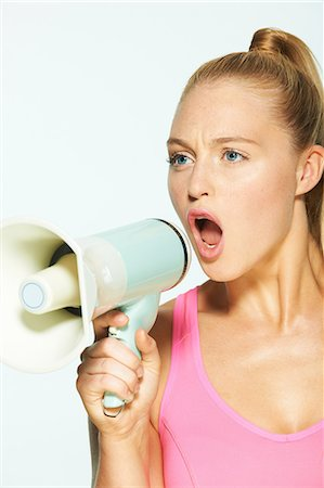 Young woman shouting through megaphone Stock Photo - Premium Royalty-Free, Code: 614-06169480