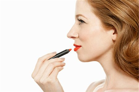 Woman applying red lipstick Stock Photo - Premium Royalty-Free, Code: 614-06311593