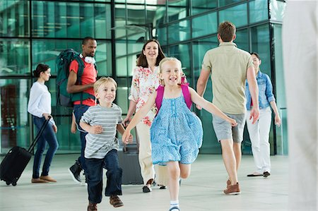 Excited children running on airport concourse Stock Photo - Premium Royalty-Free, Code: 614-06311624