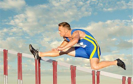 Male hurdler clearing hurdle Stock Photo - Premium Royalty-Free, Code: 614-06311625