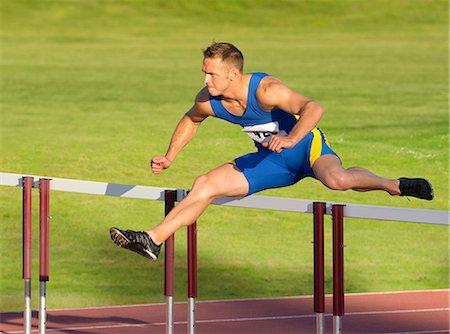 Male hurdler clearing hurdle Stock Photo - Premium Royalty-Free, Code: 614-06311626