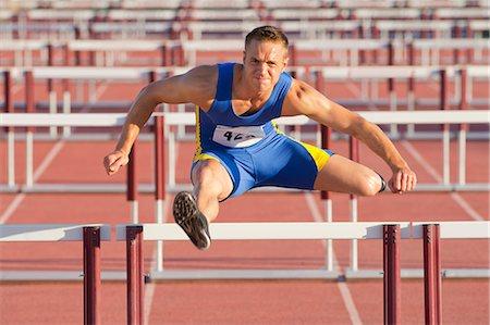 Male hurdler clearing hurdles Stock Photo - Premium Royalty-Free, Code: 614-06311627
