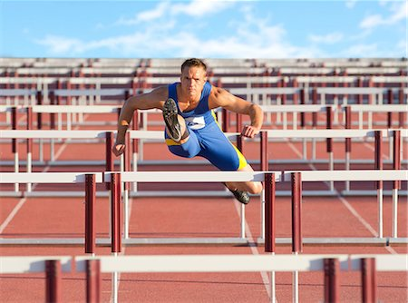 Male hurdler clearing hurdles Stock Photo - Premium Royalty-Free, Code: 614-06311628