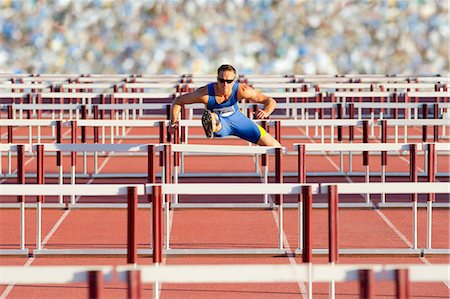 Male hurdler clearing hurdles Stock Photo - Premium Royalty-Free, Code: 614-06311629