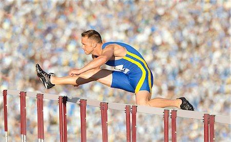Male hurdler cleaning hurdle Stock Photo - Premium Royalty-Free, Code: 614-06311634