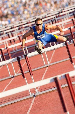 Male hurdler clearing hurdles Stock Photo - Premium Royalty-Free, Code: 614-06311630