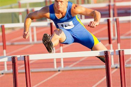 Male hurdler jumping over hurdle Stock Photo - Premium Royalty-Free, Code: 614-06311631