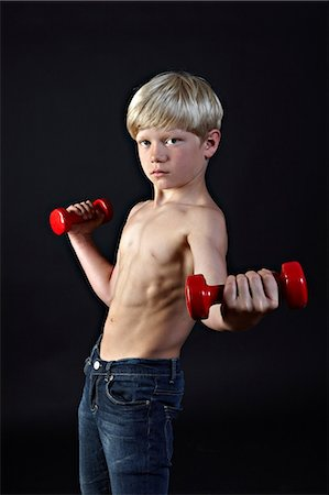 Boy lifting hand weights Stock Photo - Premium Royalty-Free, Code: 614-06311719