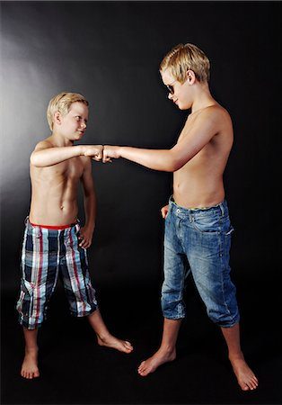 Brothers doing high five with fists Stock Photo - Premium Royalty-Free, Code: 614-06311725