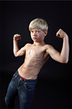 Boy flexing muscles Stock Photo - Premium Royalty-Free, Code: 614-06311720